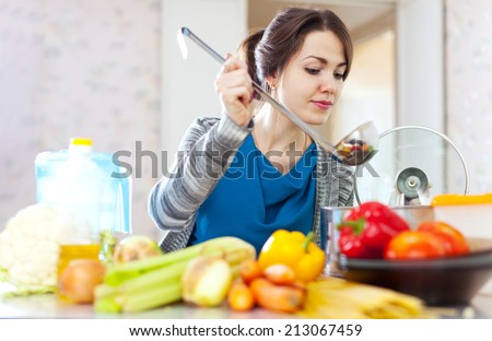 beautiful housewife cooking with ladle at her kitchen    - stock photo