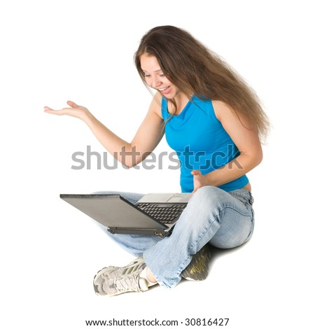 Beautiful joyful girl sits on a floor with the laptop, isolated on white