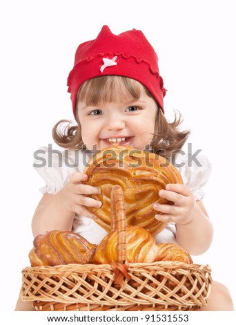 beautiful little baby in a cap eating a loaf of bread - stock photo