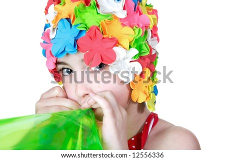 Beautiful little girls in a flowered swim cap blowing up a bright green inner tube - stock photo