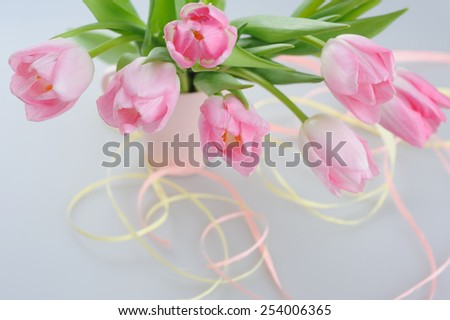 Beautiful pink tulips in a vase with decorative paper  - stock photo