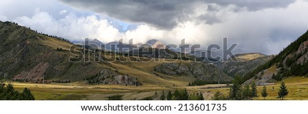 beautiful plain on the backdrop of steep mountains in the rays of the evening sun. summer landscape. the panorama - stock photo
