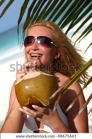 Beautiful pretty blondy woman holding coconut in tropical beach - stock photo