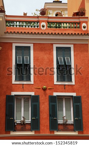 Beautiful red stucco house with old french green shutter windows and roof balcony in Monaco, Monte Carlo.  - stock photo