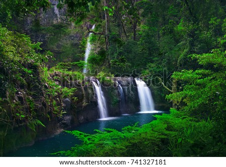 Beautiful Scenery Of Waterfalls Tumbling Down The Moss Covered Cliffs By Mountainside With Green