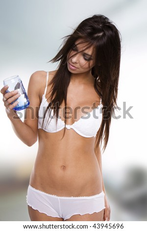 Beautiful sexy girl in lingerie holding a glass of water - stock photo