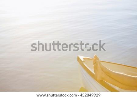 beautiful sexy women's feet on the boat - stock photo