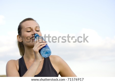 beautiful sporty caucasian girl drinking water after exercise - stock photo