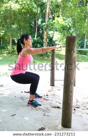 Beautiful strong woman doing squat exercise by the exercise bar in the park - stock photo
