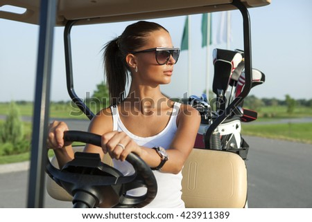 Beautiful stylish woman driving a golf car - stock photo