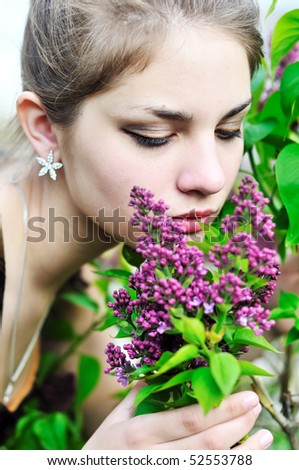 Beautiful teen girl smelling lilac blossoms - close up - stock photo