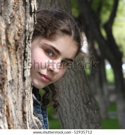 beautiful teenager girl is hiding  behind  the tree - stock photo