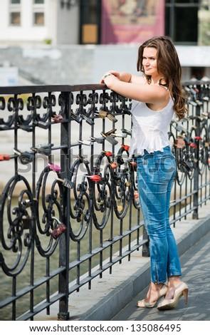 beautiful thoughtful woman near fence with wedding locks - stock photo