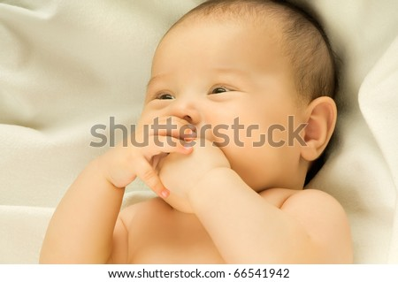 beautiful , very little kid , lie  on textile background, close face - stock photo