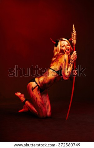 Beautiful vimpire devil with trident on deep red black - stock photo
