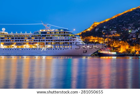 Beautiful white giant luxury cruise ship on stay at Alanya harbor - stock photo