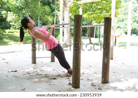 Beautiful woman doing pull up on exercise bar in a park - stock photo