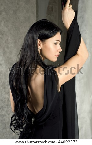 Beautiful woman in a black dress with the bared back - stock photo