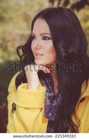Beautiful woman in nature looking away. Portrait of beautiful caucasian woman sitting on bench in park, thoughtfully looking away. Done with a vintage retro filter. - stock photo