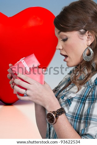 Beautiful woman opening a Valentines day present - stock photo