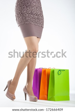 Beautiful woman's legs and multicolored shopping bags on white background