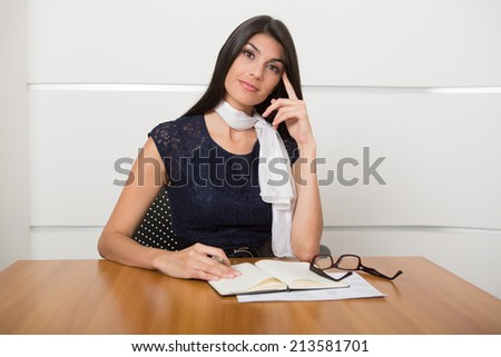 Beautiful woman thoughtfully  with a pen in her hand looking