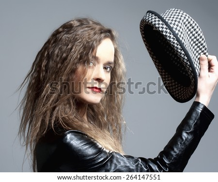 Beautiful Woman with Brown Curly Hair Holding a Hat - stock photo