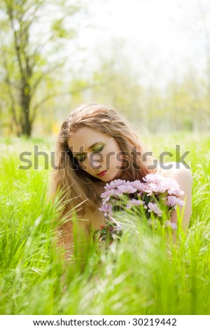 beautiful woman with flowers sitting on green grass