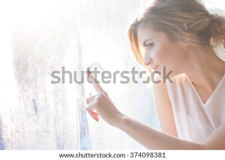 beautiful woman with fresh daily makeup and romantic wavy hairstyle, sitting at the windowsill, draws on glass - stock photo