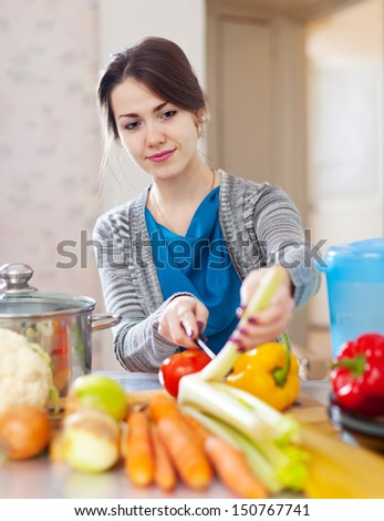 beautiful woman with green celery anf other vegetables in her kitchen at home - stock photo