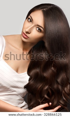 Beautiful woman with Healthy Brown Hair.  Beauty Model brunette girl touching her long smooth shiny hair. Gorgeous Hair. Hairstyle. Hair cosmetics, haircare.  - stock photo