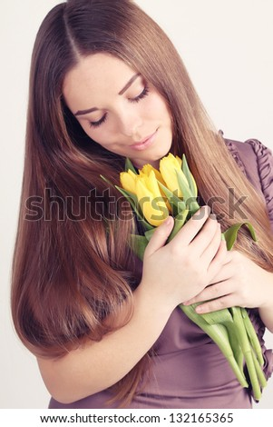 Beautiful woman with long hair with yellow tulips - stock photo