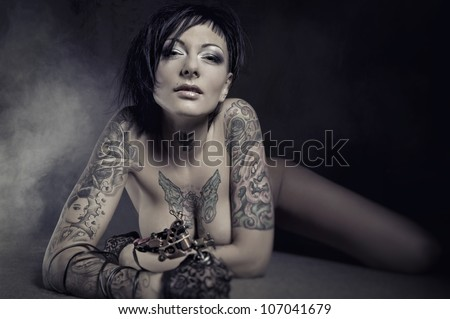 Beautiful woman with many tattoos posing indoors - stock photo