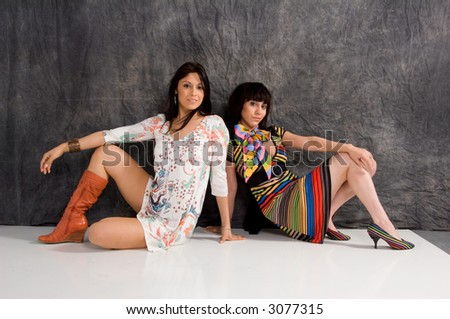 2 beautiful women posed back to back one dressed in a modern dress and one in a retro pop art pattern outfit - stock photo