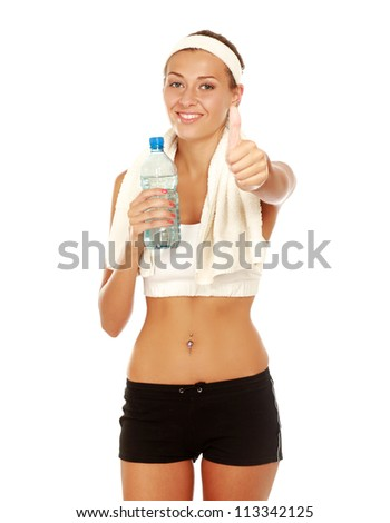 Beautiful young athlete with bottle of water and towel on her shoulders