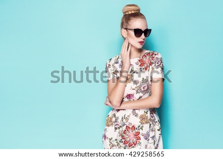 beautiful young blonde woman in nice spring dress, elegant black sunglasses posing in a studio. Fashion spring summer photo - stock photo