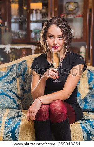 Beautiful young brunette woman drinking champagne. Gorgeous girl holding a glass of champagne. - stock photo