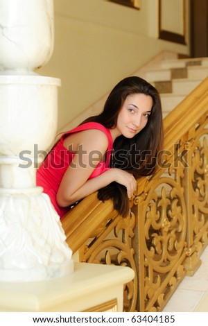 beautiful young girl on a ladder in red dress - stock photo