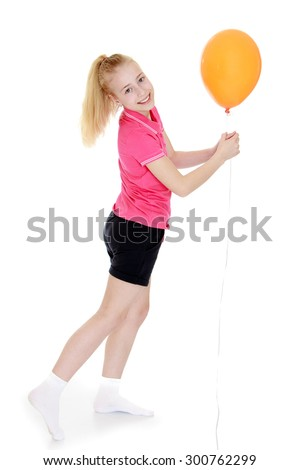 Beautiful young girl with long, thick blond tail in a pink t-shirt with short sleeves and black shorts. Girl in white socks holding hands orange balloon , photo dynamics-Isolated on white background - stock photo