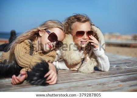 2 beautiful young teen girls friends having fun lying on board in sun glasses and coats - stock photo