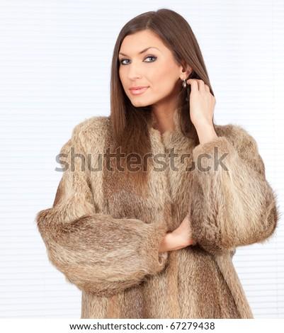 beautiful young woman in a fur coat - stock photo