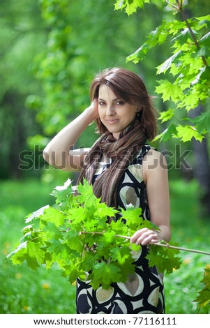 beautiful young woman in a park holding a branch - stock photo