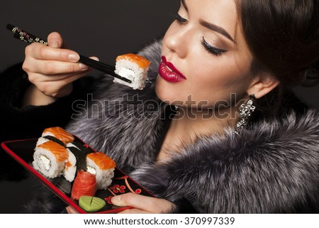 Beautiful young woman is eating sushi over black background - stock photo