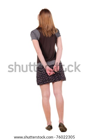 Beautiful young woman looking at wall. Rear view. Isolated over white. - stock photo