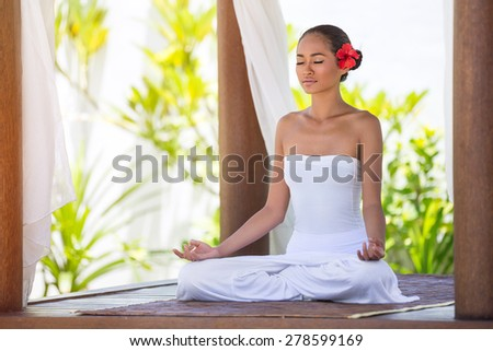 Beautiful young woman meditating with eyes closed - stock photo