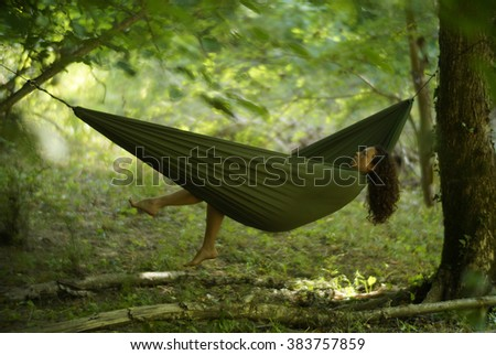 Beautiful young woman relaxing in a hammock deep in the woods.                               - stock photo