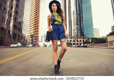 Beautiful young woman wearing hat, sunglasses, shorts, tropic top and fringe handbag, standing on the street. Fashion photo