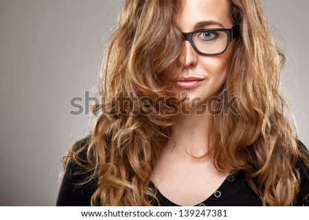 Beautiful young woman with glasses in studio/ Close up of a normal girl with healthy hair