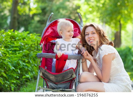 Beautiful young woman with her child in a baby carriage in the park - stock photo
