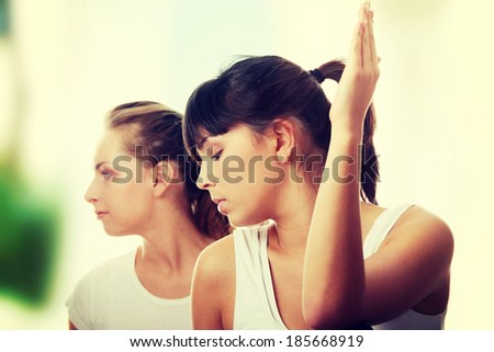 2 Beautiful young womans doing yoga exercise , isolated - stock photo